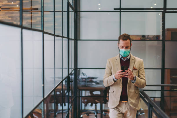 Safety in the office during COVID-19 pandemic, businesspeople with face masks stock photo