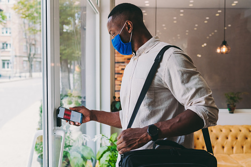 Businessman leaving the office is using smartphone-key to unlock the door