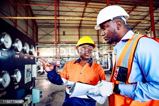 Africa, Industry, Business, Steel Factory, People - Skilled Factory Workers Inspecting Industrial Equipments at a Factory in Africa.