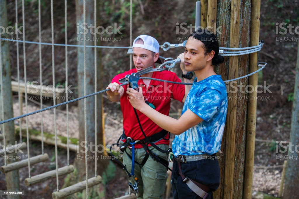 Safety instructor preparing a man to go on a zip line through the forest stock photo