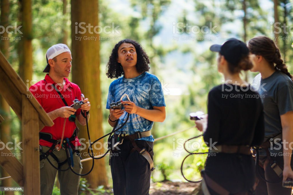 Safety instructor teaching a small group of people how to use a safety harness stock photo