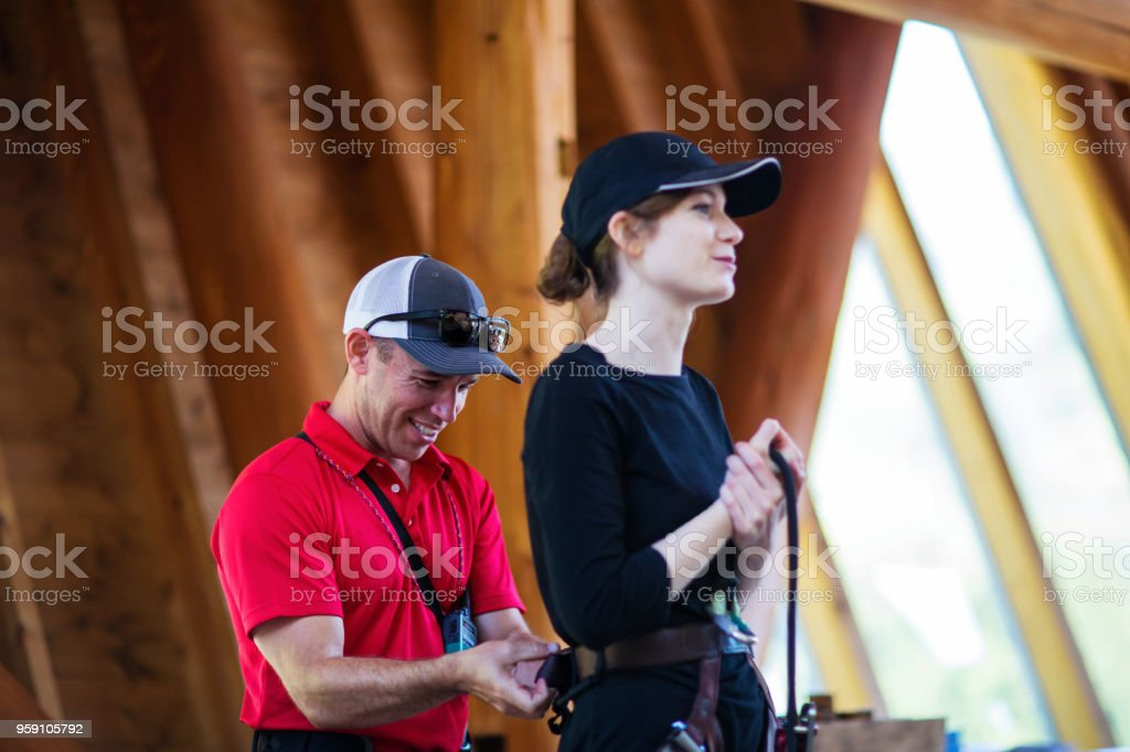 Safety instructor teaching a woman how to use a safety harness for an obstacle course stock photo