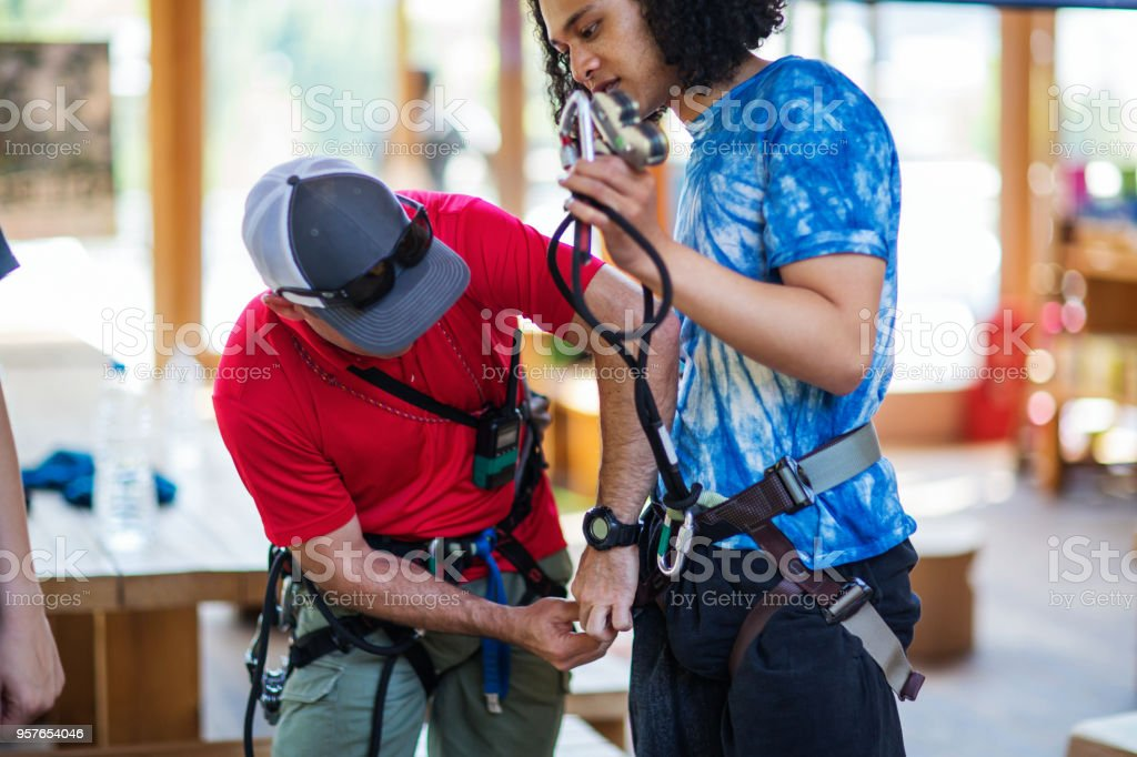 Safety instructor teaching how to use a safety harness for an adventure park stock photo