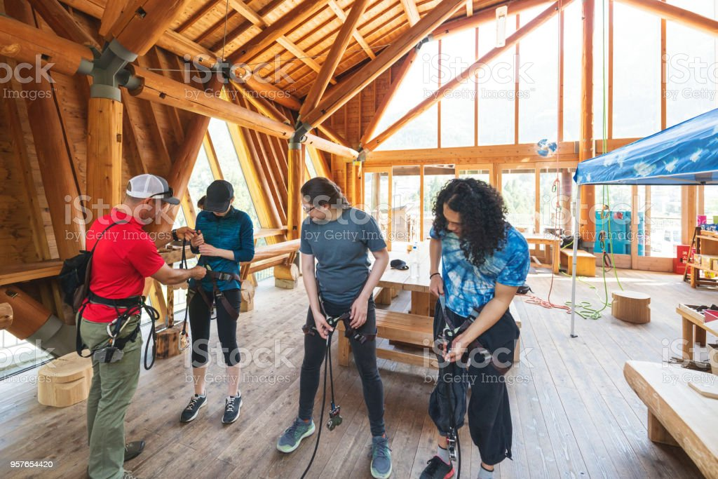 Safety instructor teaching how to use a safety harness to a small group of people stock photo