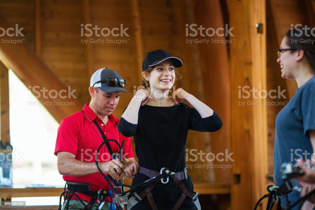 Safety instructor teaching women how to use a safety harness for an obstacle course stock photo