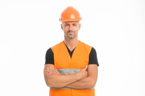 Safety is main point. Man protective hard hat and uniform white background. Worker builder confident looking camera. Protective equipment concept. Builder crossed hands chest. Strong handsome builder stock photo