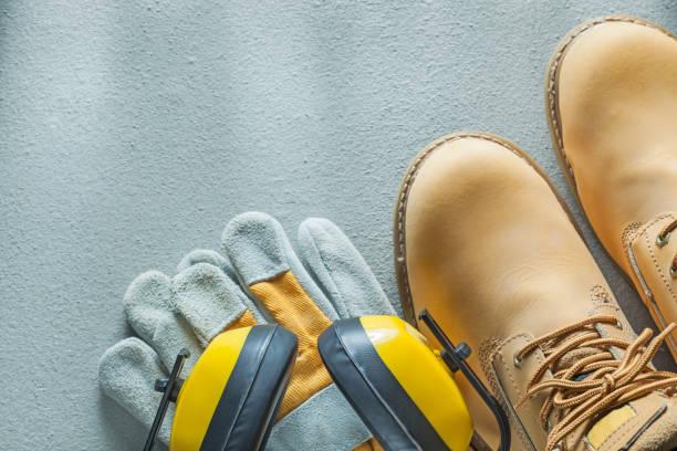 sicherheit spitzen stiefel tragen von schutzhandschuhen ohrenschützer auf konkrete hinterg - diy leder stock-fotos und bilder