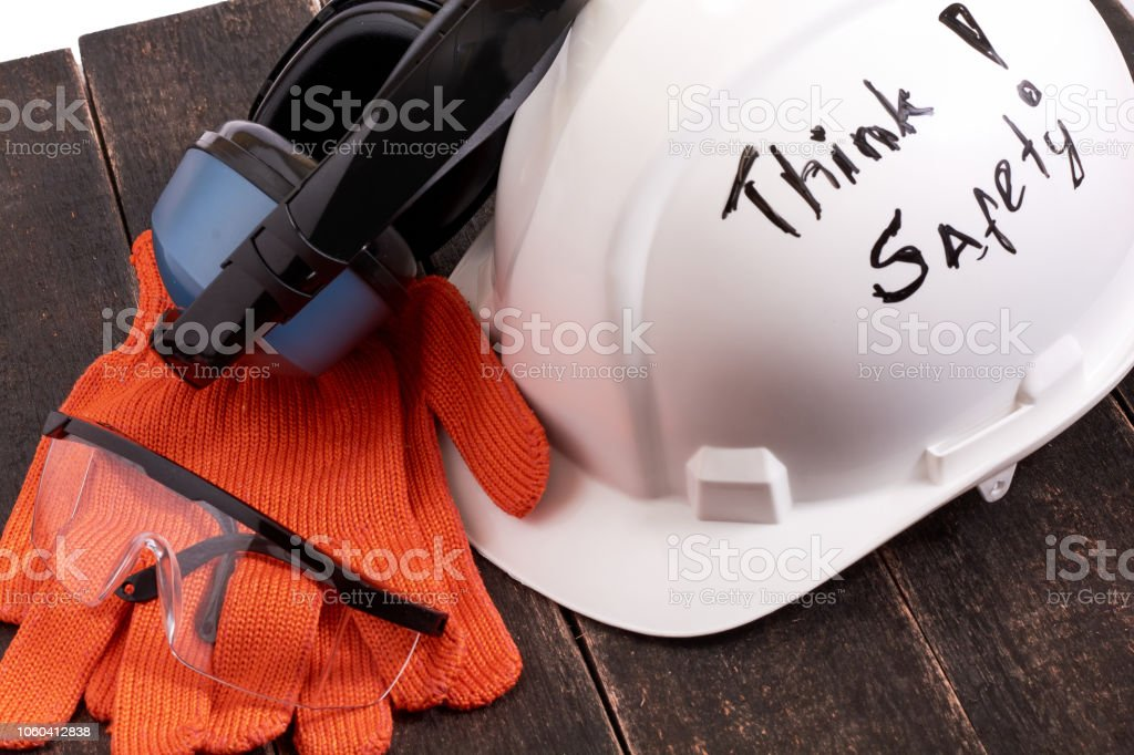 Safety personal protective equipment on a black wooden table on white...