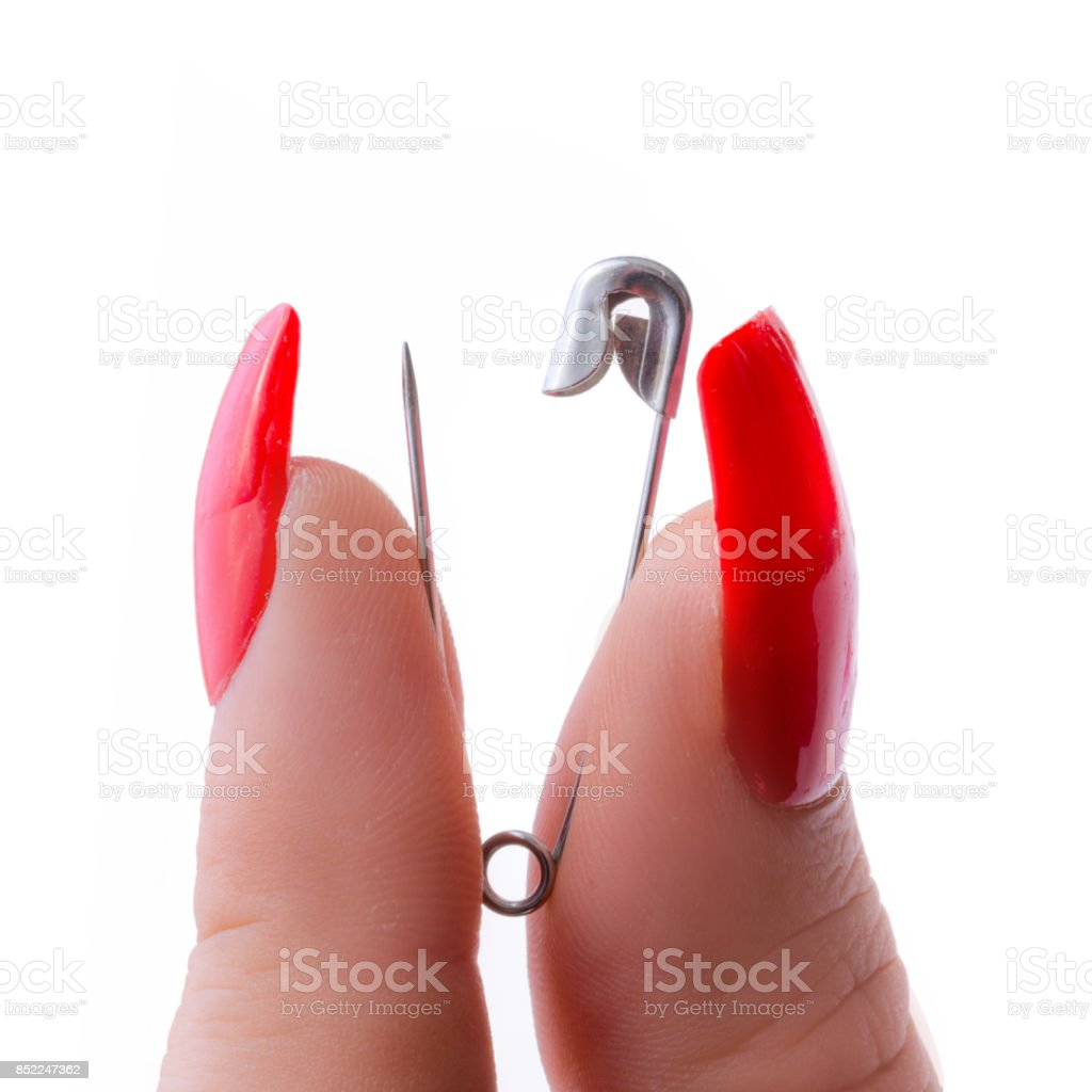 safety pin between two long nailed fingers – zdjęcie