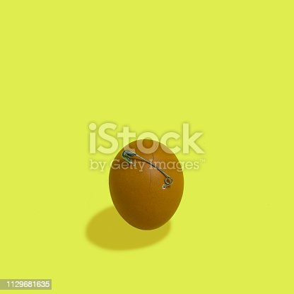 Safety pin holds together cracked egg. Minimal style. Creative idea, imagination and fantasy. Unexpected Easter concept