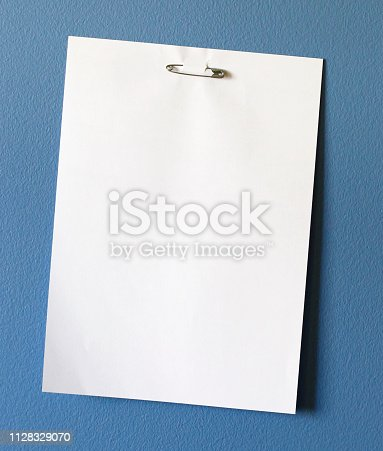 A blank sheet of white paper pinned by a safety pin to a blue surface.