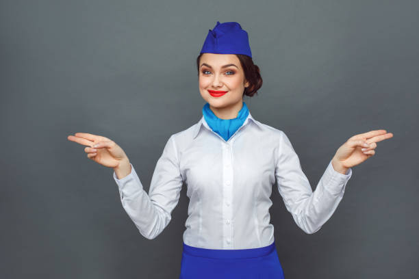 Safety Regulations. Stewardess standing isolated on grey showing emergency exit aside looking camera confident Young woman professional stewardess standing isolated on grey wall explains safety regulations hands aside showing emergency exit looking camera smiling confident air stewardess stock pictures, royalty-free photos & images