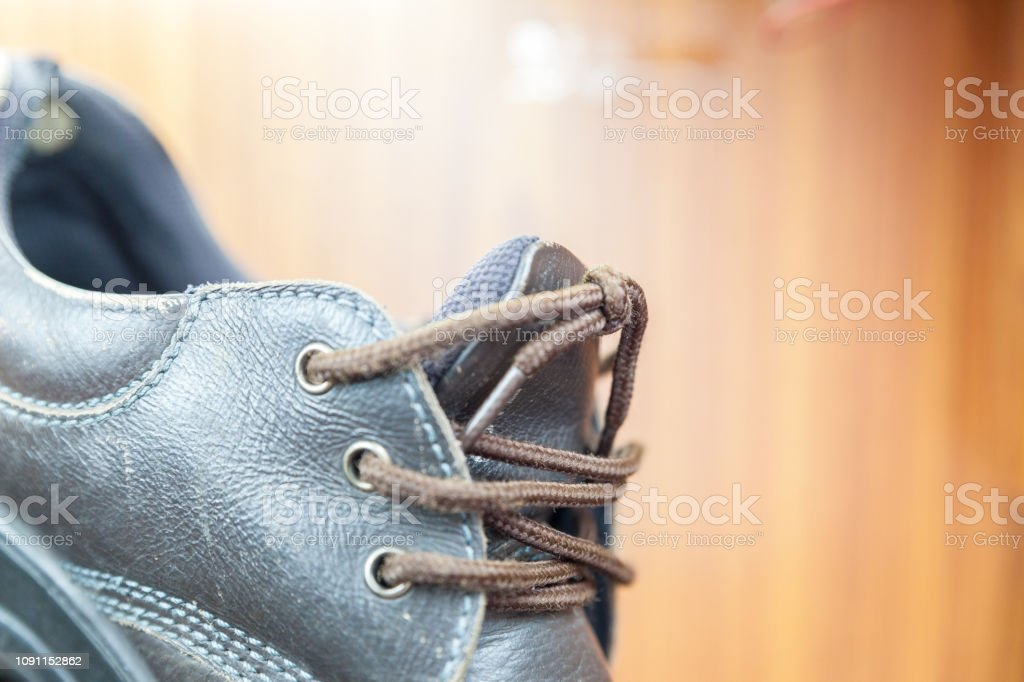 Safety shoes is damaged on wooden background.