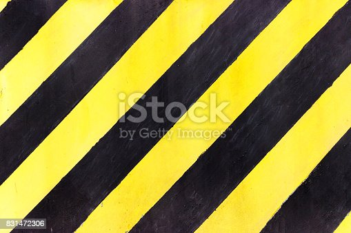 97709303 istock photo Safety stripes on construction site, Black and yellow Under construction sign over a grunge texture, top view 831472306