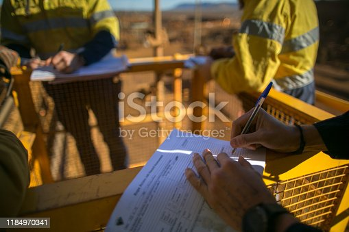 Miner supervisor checking reviewing document before issued sigh of working at height permit JSA risk assessment on site prior to performing high risk work on construction mine site, Perth, Australia