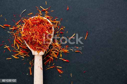 Saffron in spoon on a dark background, selective focus, macro shot, shallow depth of field