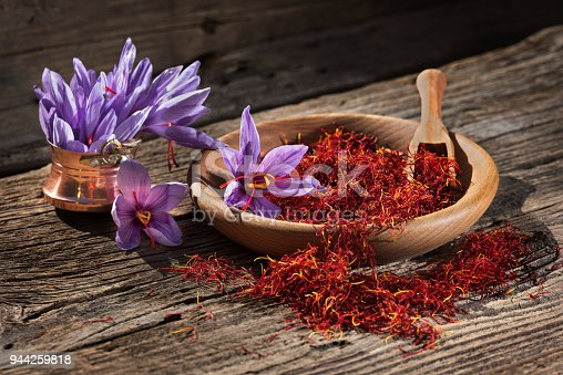 istock Saffron in wooden bowl on wooden table with saffron flowers on the side 944259818