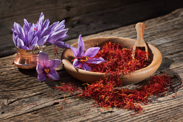Saffron in wooden bowl on wooden table with saffron flowers on the side Set of dry saffron spice and fresh saffron flowers saffron stock pictures, royalty-free photos & images