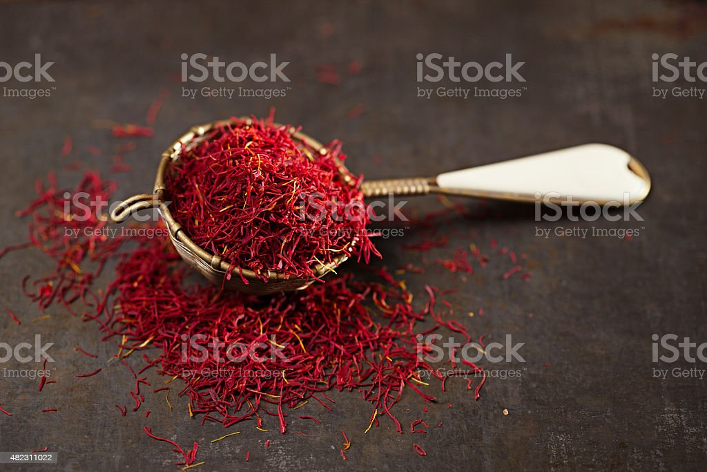 saffron spice threads and powder  in vintage  old sieve stock photo