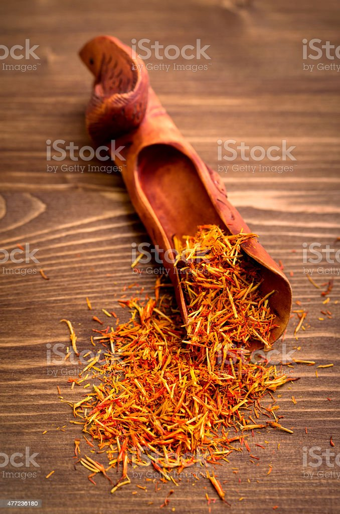 Saffron spice threads in scoop on wooden background stock photo