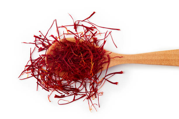 Saffron spice threads Saffron spice threads (strands) in wooden spoon isolated on white background saffron stock pictures, royalty-free photos & images