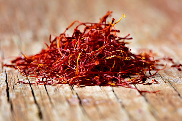 saffron threads a pile of saffron threads on a rustic wooden table saffron stock pictures, royalty-free photos & images