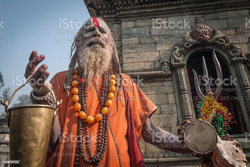 Saffron-robed Sadhu, Pashupatinath with Alms Bucket and Trident, Kathmandu, Nepal stock photo