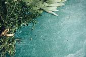 Bunch of fresh sage and oregano on a green chalkboard