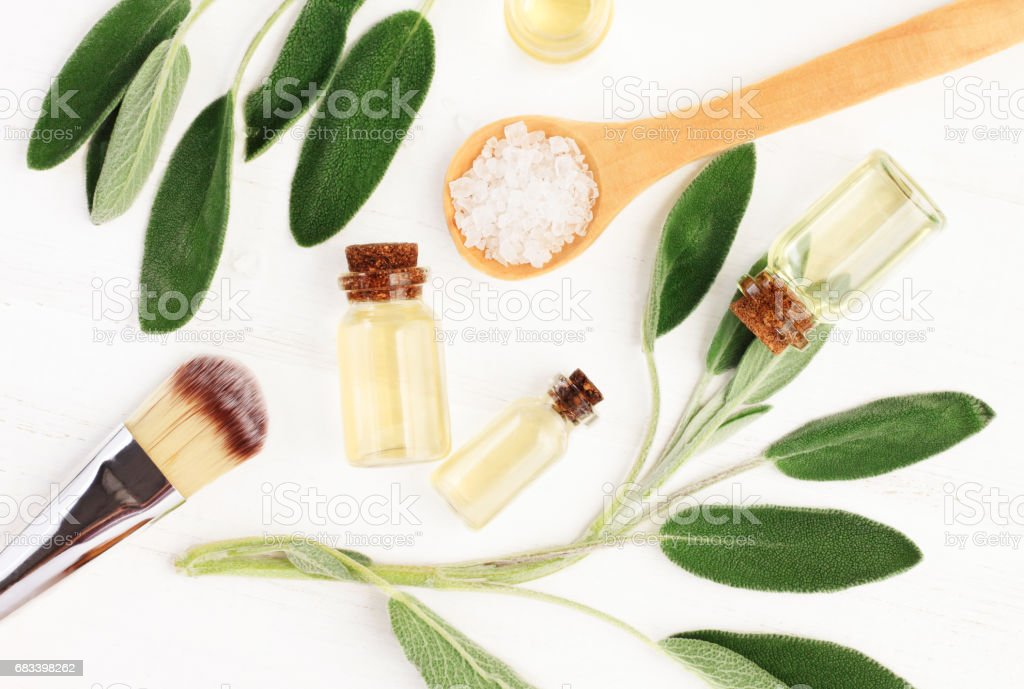 Sage essential oil (Salvia officinalis) leaves and aroma oil bottles. stock photo