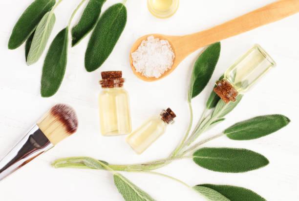 Aceite esencial salvia (Salvia officinalis) hojas y botellas de aceite de aroma. - foto de stock