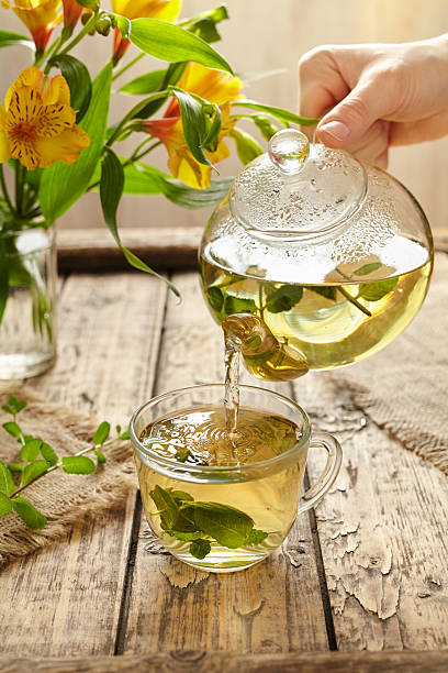 Sage tea pouring in glass transparent cup from teapot stock photo