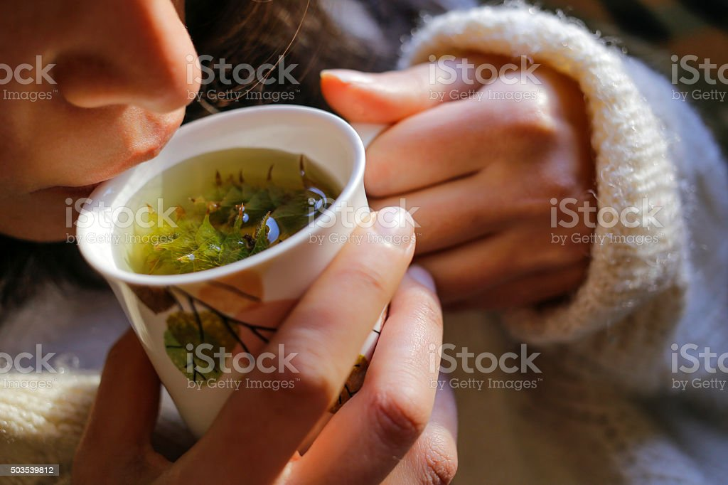 Sage tea with woman hand and woman lips stock photo