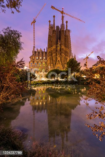 A vertical colorful sunset view of the east Nativity facade of The Basílica de la Sagrada Família, reflected in a small pond. Barcelona, Catalonia, Spain.