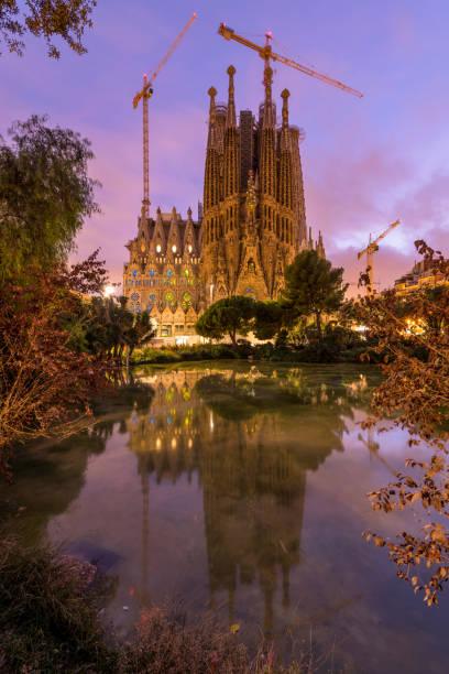 Sagrada Familia - A vertical colorful sunset view of the east Nativity facade of The Basílica de la Sagrada Família, reflected in a small pond. Barcelona, Catalonia, Spain. stock photo