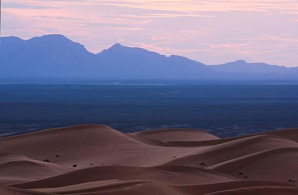 Sahara desert dunes and mountains at dusk stock photo