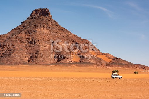 A 4x4 car in the typical landscape of the remote Ennedi Mountains (massif) in the Sahara desert, North-East Chad. The Ennedi massif was declared as an UNESCO World Heritage site in 2016.