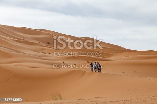 Errachidia Province, Morocco - October 17, 2015: group of people walk along the sand dunes in the Sahara Desert.