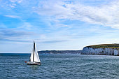 Sailing Yacht sailing in the English Channel off the white cliffs in calm water with blue sky and some cloud