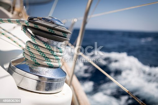A winch on a sail boat is used to tighten the rope of the front sail. Selective focus on the rope itself, the photograph was taken while the sail boat is under strong wind conditions, with which you can notice the breaking waves and foams in the background.