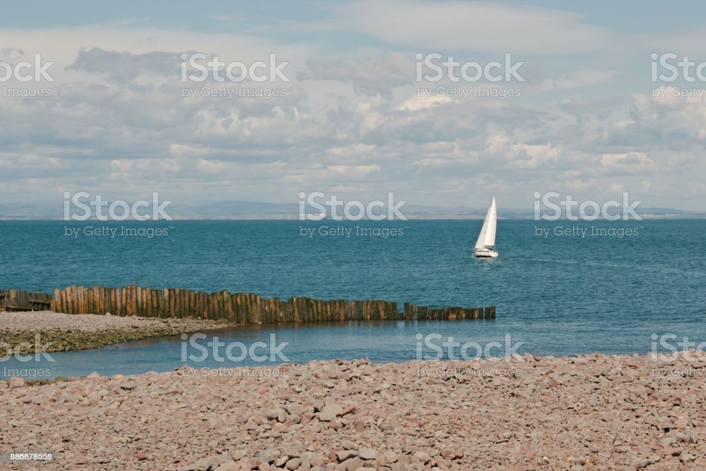 A sail boat with full sail set on the sea. stock photo
