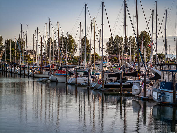 sail boats and yachts anchored in marina stock photo