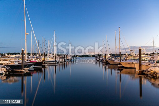 Sail boats docked in the harbor reflecting in water during blue hour. in New Castle, NH, United States