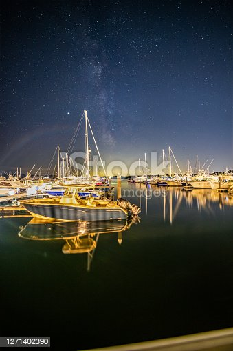 Sail boats docked in the harbor reflecting under the milky way sky. in New Castle, NH, United States