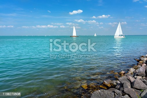Sail boats on Lake Balaton with rocks on the coastline