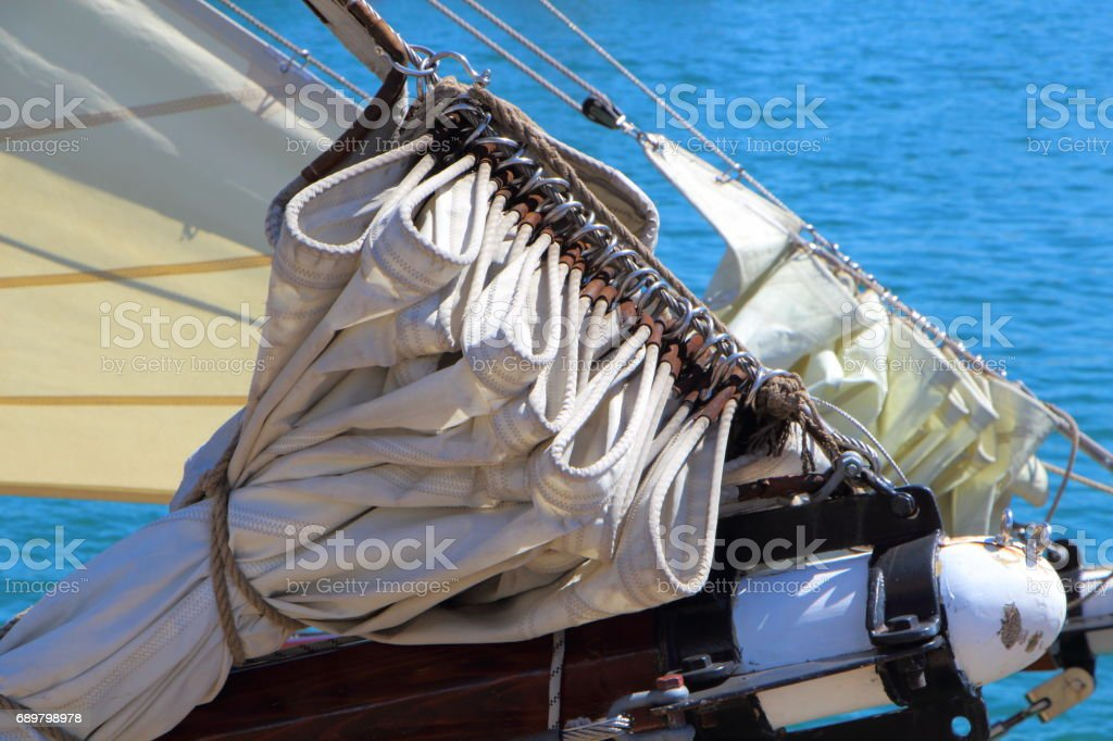 Sail folded back on the boom of a sailboat stock photo