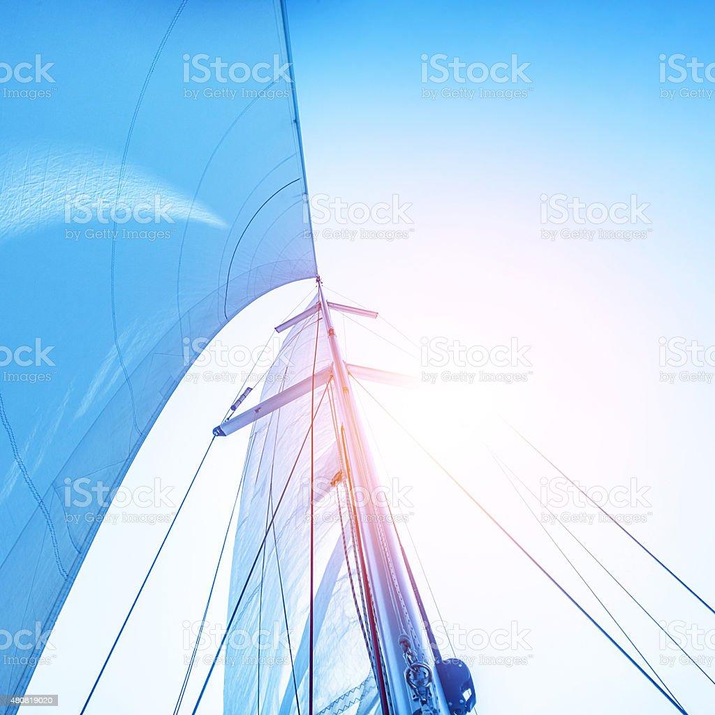 Sail on blue sky backdrop stock photo