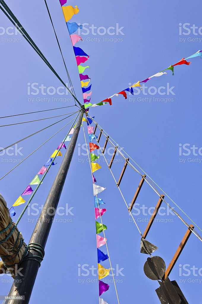 Sail rolled-up with colorful flag stock photo