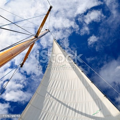 sail yacht mast with white sail against dark blue sky