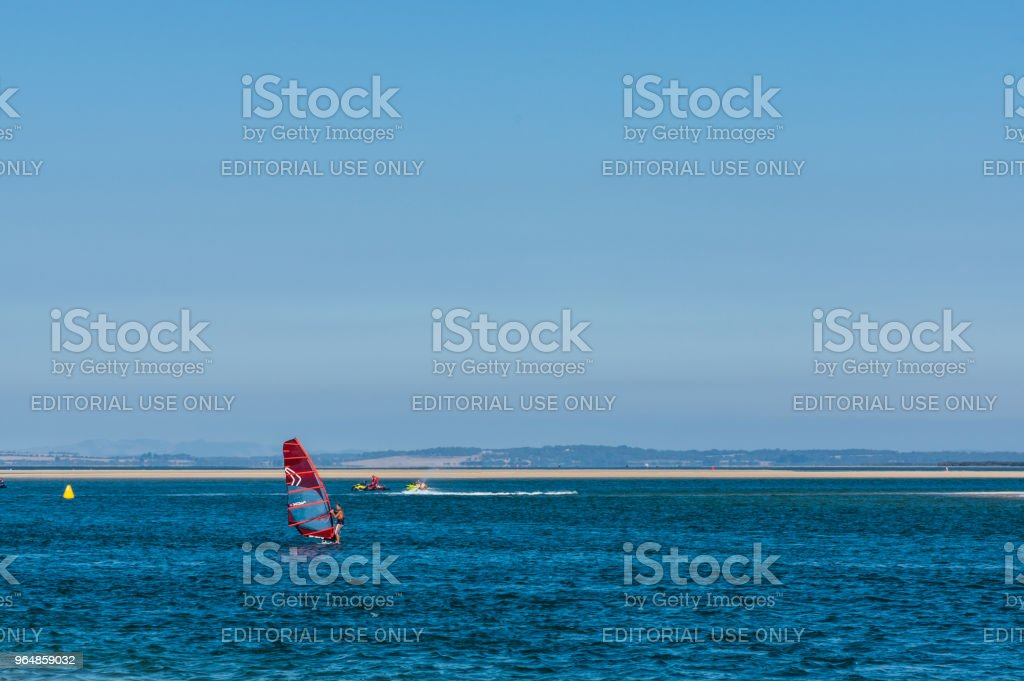 Sailboarder and personal water craft off Inverloch beach in South Gippsland. royalty-free stock photo