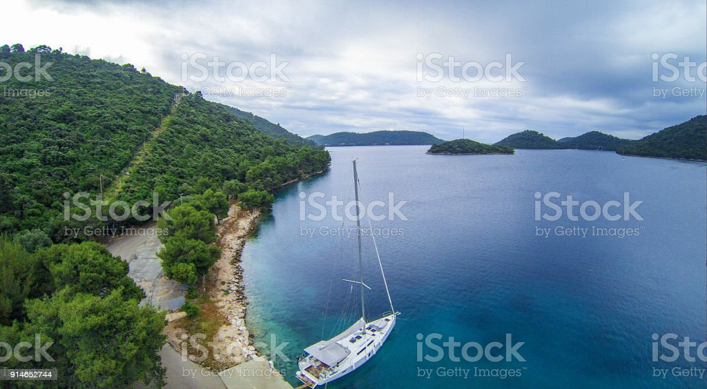 Sailboat Anchored on the Coastline, Aerial View stock photo